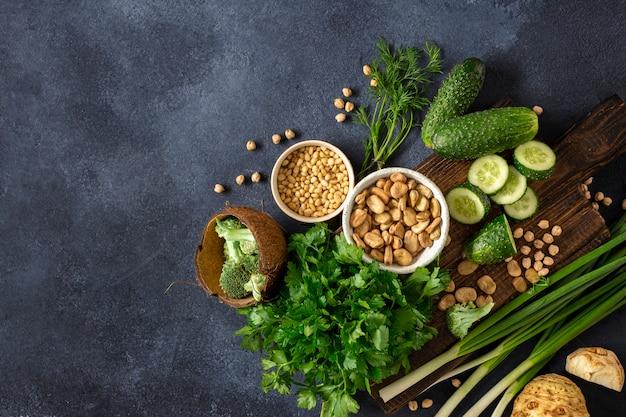 健康的なビーガンフードのコンセプトです。新鮮な野菜、ハーブ、シリアル、暗い背景の上面のナッツ。野菜料理