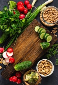 健康的なビーガンフード野菜料理のコンセプトです。暗い背景の上面に新鮮な野菜、ハーブ、シリアルと木製のまな板キッチンボード