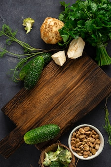 メニュー食品の背景。暗い背景の上面にビーガンフードを調理するための食材を使った素朴な木製のまな板