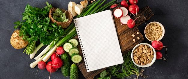 ダイエット食品のコンセプト。健康なビーガン食。新鮮な野菜、ハーブ、シリアル、ナッツの空白のノートブック。野菜料理