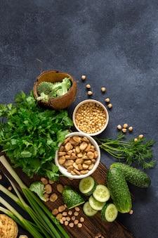 健康食品のきれいな食事のコンセプトです。緑の野菜、ハーブ、シリアル、暗い背景の上面にナッツ