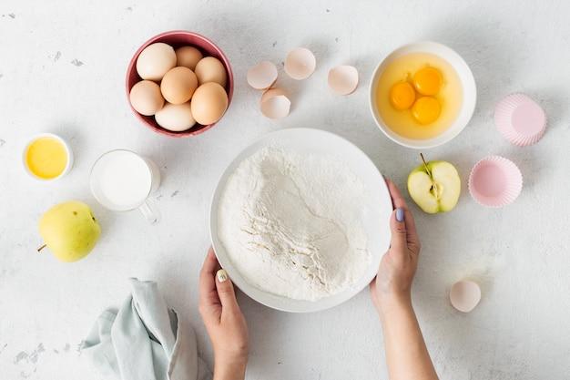 自家製アップルパイの生地を調理する材料を焼きます。女性準備マフィン。