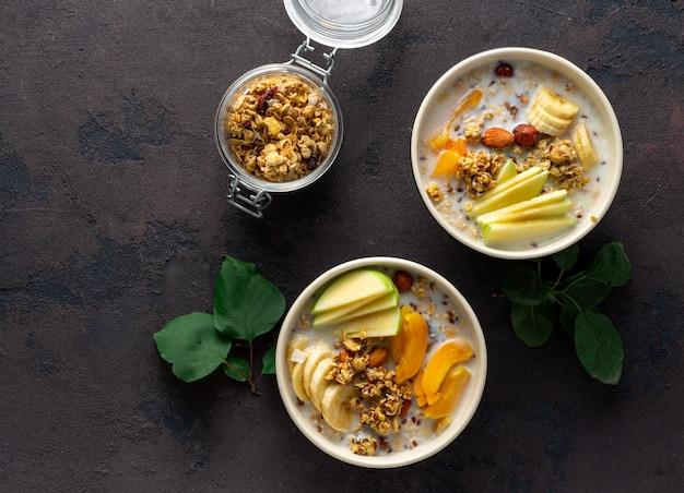 フルーツ、ナッツ、ミルク、ピーナッツバターをボウルに入れたグラノーラの朝食。健康的な朝食シリアルトップビュー