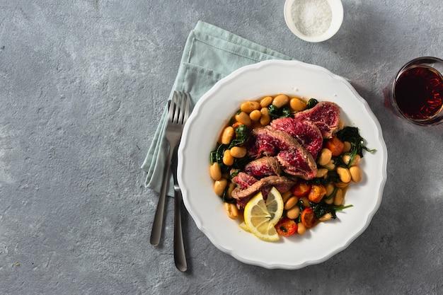 ビーフステーキ、白豆、ほうれん草、トマトのディナープレートトップビューコピースペース