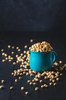 ボウルひよこ豆は暗い木製のテーブルのクローズアップ