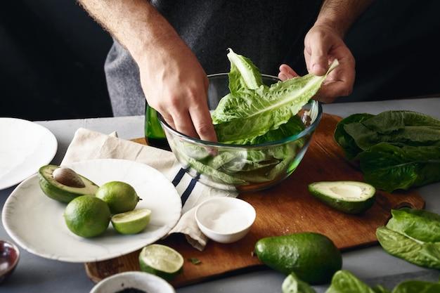 健康的なダイエット食品のコンセプトを調理します。緑の野菜のサラダを調理する男