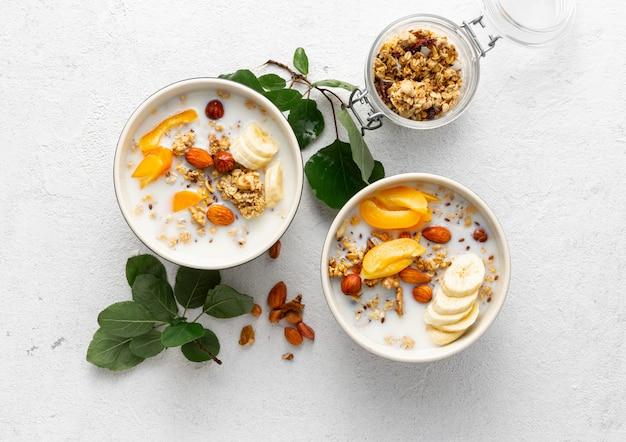 Гранола фрукты с молоком, арахисовое масло в миске, здоровые хлопья для завтрака вид сверху