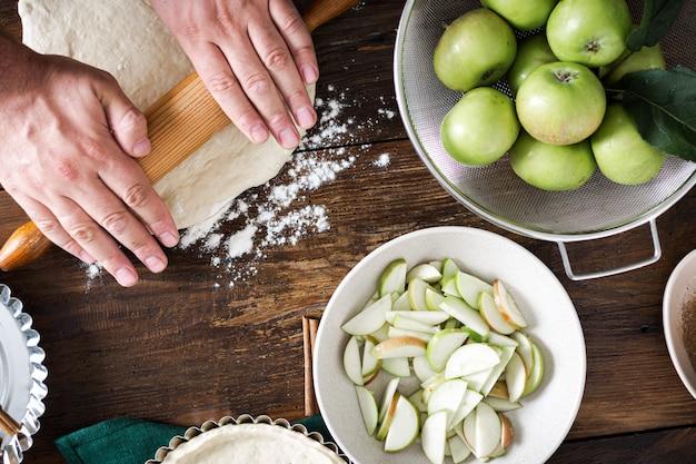 木製テーブルトップビューで自家製フランスアップルパイを調理する男