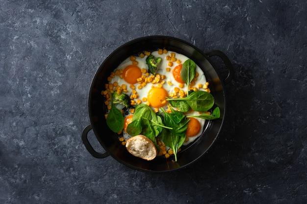 ほうれん草とトウモロコシの暗い石のテーブルトップビューでフライパンの卵と健康的な朝食用のテーブル