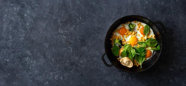 ほうれん草とトウモロコシの暗い石背景トップビューでフライパンの卵と健康的な朝食用のテーブル