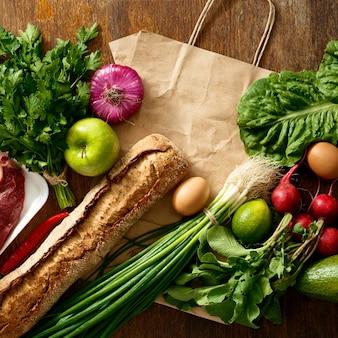 Бумажный пакет разных здоровой пищи деревянный стол