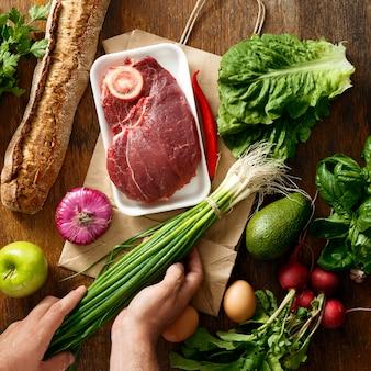 Вид сверху бумажный пакет разнообразие здоровой пищи деревянный стол
