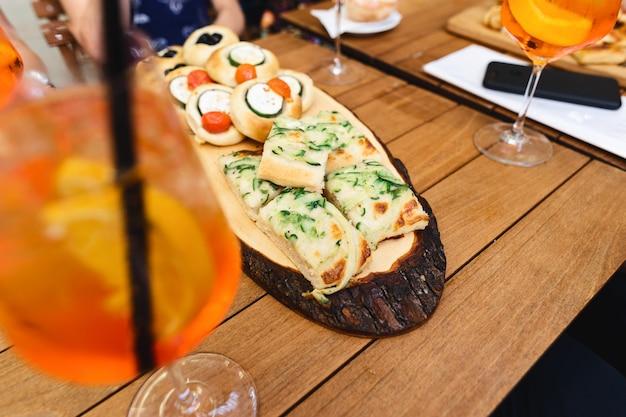 カフェの木製テーブルでカクテルアペロールスプリッツと様々なスナック