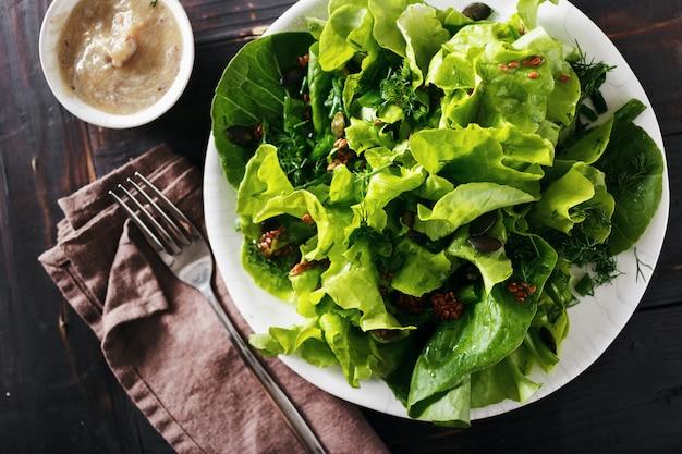 プレート新鮮なグリーンサラダ亜麻の種子ダーク木製ダイエット食品