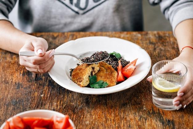 昼食を持つ女性揚げプルーンエンバクカツレツキノア
