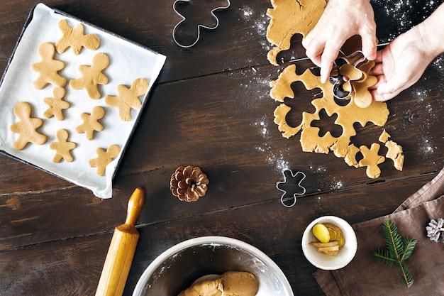 Рождественская еда человек приготовления пряников печенье вид сверху рождественский десерт