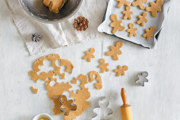 Рождественская еда сырое тесто приготовление пряничный человечек печенье вид сверху рождество десерт плоская планировка
