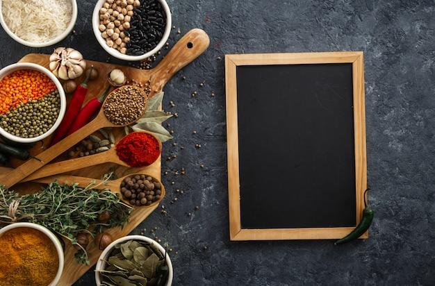 メニュー黒板にご飯、スパイスとハーブのトップビュー、暗い背景にさまざまな豆