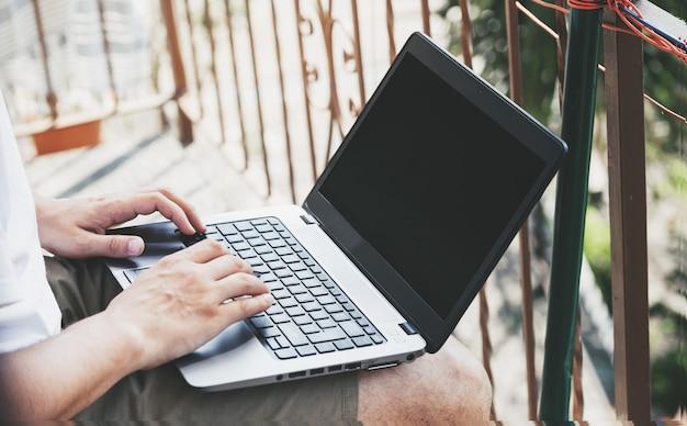 彼のバルコニーで自宅でラップトップを使用している人。ワークスペース。外で働く