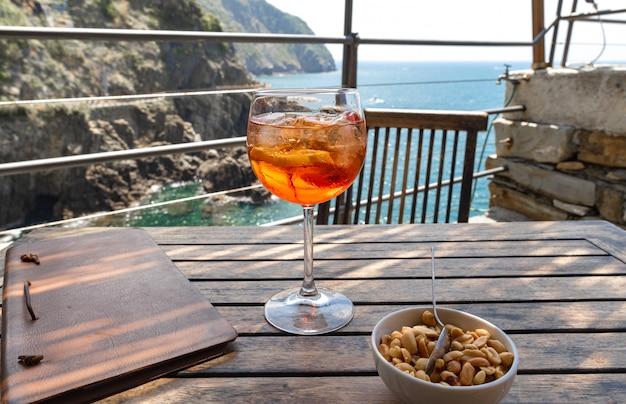 アペロールスプリッツカクテルは、レストランの木製テーブルの上にクローズアップ。チンクエテッレ、イタリアのリオマッジョーレ