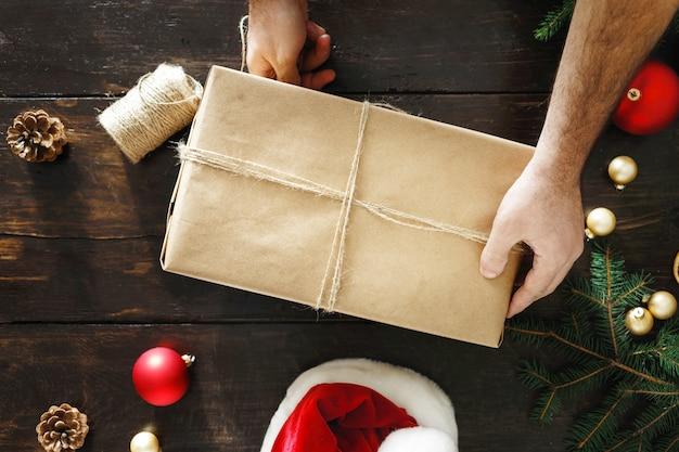 Мужские руки, упаковка подарочной коробке деревянный стол, деревенские рождественские подарки, вид сверху