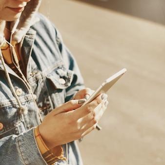 若い女性ブロガーが路上でソーシャルネットワークを閲覧します。彼女の電話で女性のテキストメッセージ