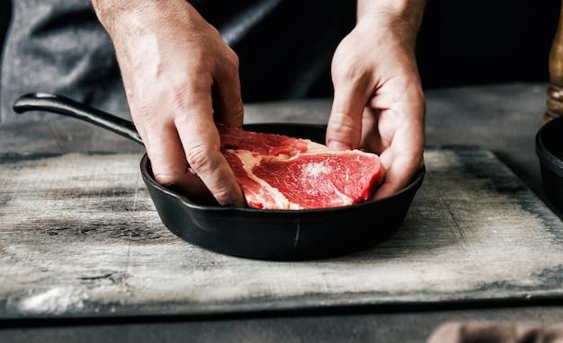 Человек готовить стейк из говядины темный фон темный стиль