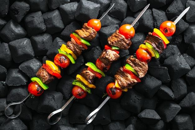 残り火トップビューでグリルされている牛肉の串焼き