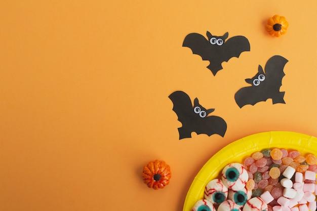 ハロウィーンのコンセプトです。黒い紙コウモリ、オレンジ色のテーブルのお菓子