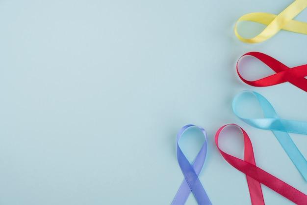 世界がんの日。明るい青の背景にカラフルなリボン癌意識