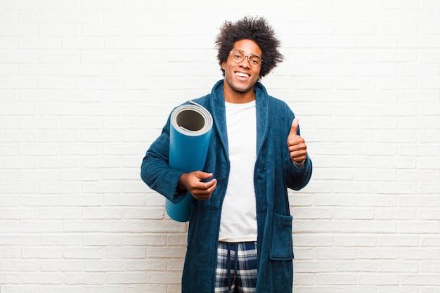 Молодой черный человек в пижаме с ковриком для йоги
