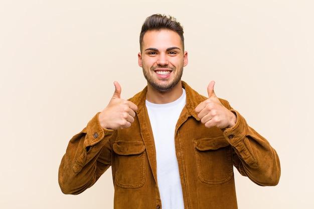 両方の親指を上にして、幸せで前向きで自信を持って成功しているように見える笑顔