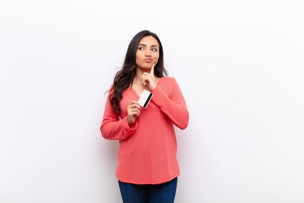 クレジットカードで平らな壁に対して若いラテン系のきれいな女性