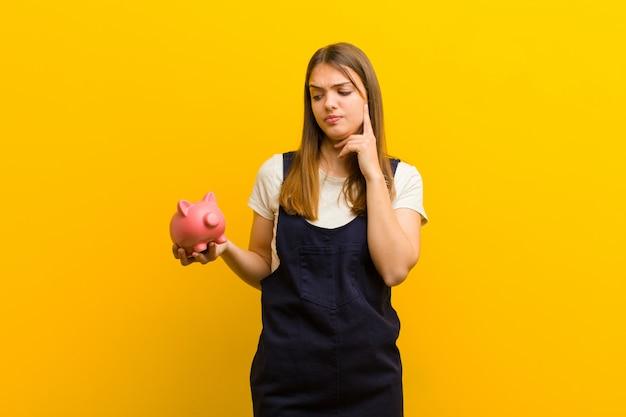 Молодая милая женщина с копилкой против оранжевой предпосылки