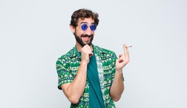 Молодой хиппи человек курит сустав против белой стене