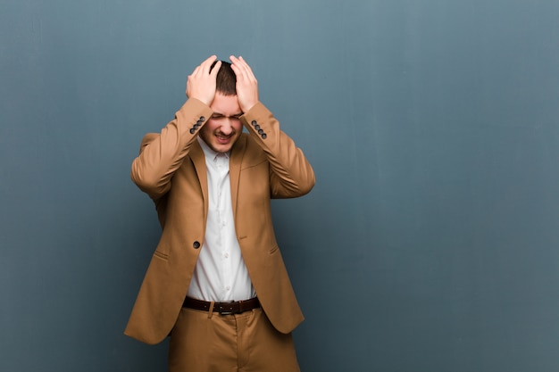 頭痛でストレスと不安、落ち込んでイライラし、両手を頭に上げている