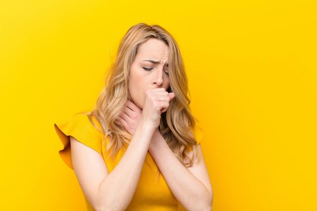 喉の痛みやインフルエンザの症状で気分が悪くなり、口を覆ったまま咳をする