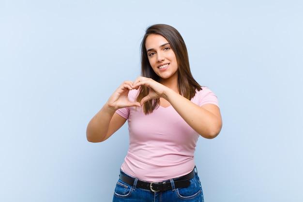 Улыбаясь и чувствуя себя счастливыми, милыми, романтичными и влюбленными, делая форму сердца обеими руками