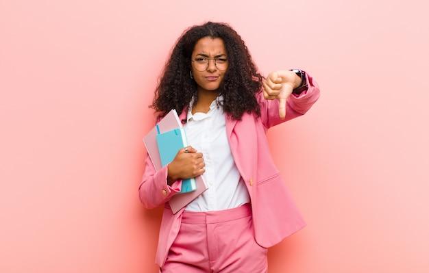 ピンクの壁に対して本を持つ若い黒かなりビジネス女性