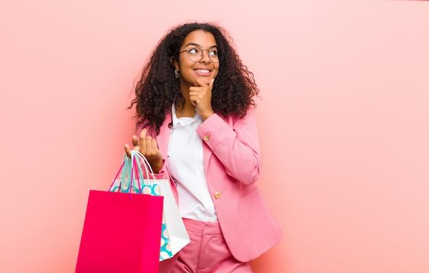 ピンクの壁に買い物袋を持つ若い黒きれいな女性