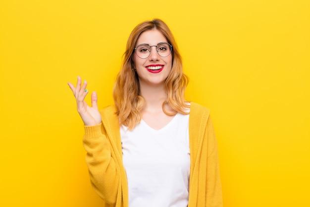 幸せ、驚き、陽気、肯定的な態度で笑顔、黄色の壁に対する解決策またはアイデアを実現する若いかなりブロンドの女性