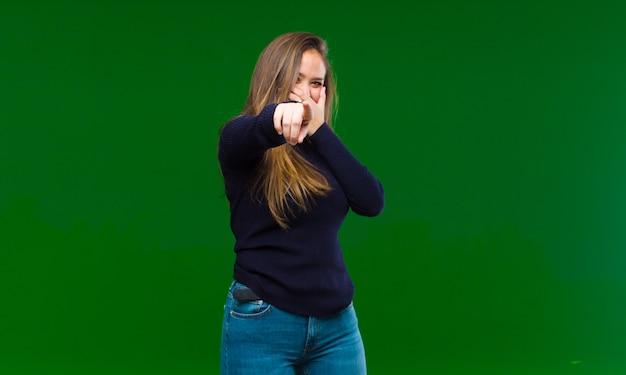 若い女性が幸せそうに笑って、横を見て、疑問に思って、考えて、または緑のアイデアを持っている