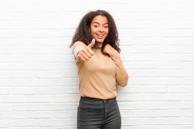 誇りに思って、屈託のない、自信を持って、幸せな若い黒人女性、レンガの壁に親指で積極的に笑顔
