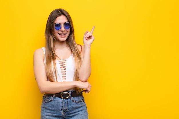 Молодая женщина счастливо улыбается и смотрит в сторону, удивляясь, думая или имея идею