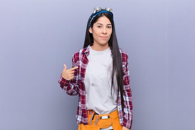 誇りに思って、自信を持って、幸せを探している若いラテン女性笑顔と自己を指すまたはナンバーワンサインを作る