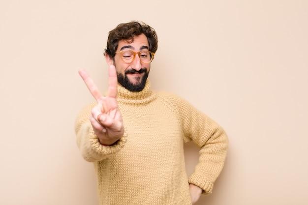 若いクールな男笑顔と幸せ、屈託のない、肯定的なジェスチャーの勝利または平壁に片手で平和を探して