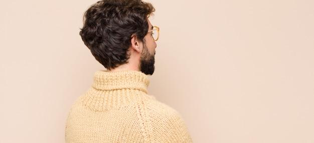 Молодой спокойный человек на виде профиля, смотрящий, чтобы скопировать пространство вперед, думая, воображая или мечтая на плоской стене