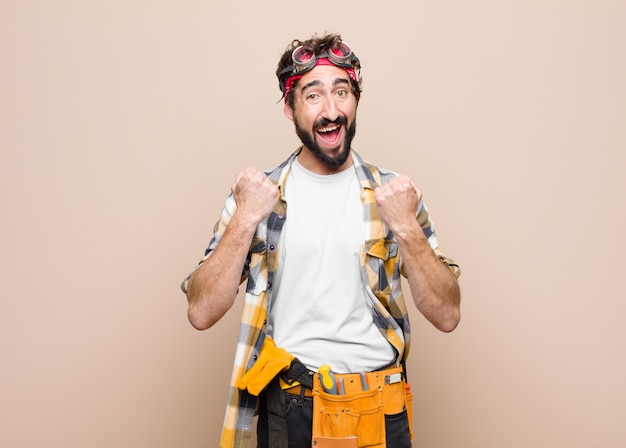 平凡な壁での成功を祝っている間、意気揚々と叫び、笑い、幸せと興奮を感じている若い家政婦の男