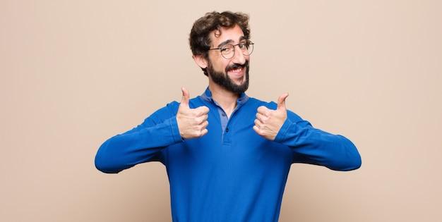 平らな壁に両方の親指で広く幸せ、肯定的、自信を持って成功した笑顔の若いハンサムな男