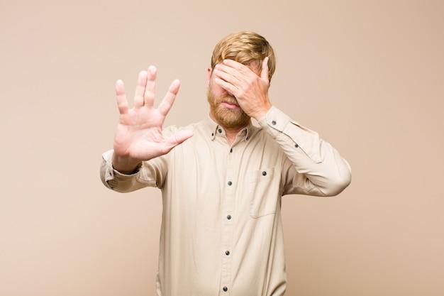 顔を手でつまんで、もう一方の手を前に出して止め、写真や写真を拒否する